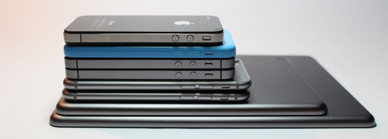 A stack of old iPhones and iPads